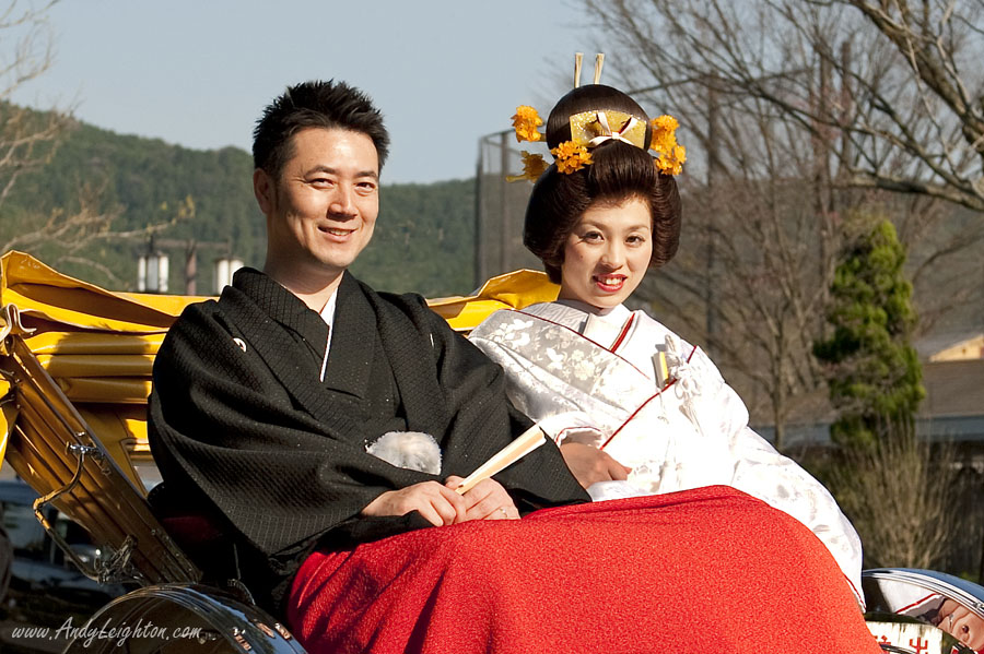 A Japanese bride and groom dressed in tradition wedding ceremony costumes ride along the footpath in a 'jinrikisha' or rickshaw in Kyoto, Japan