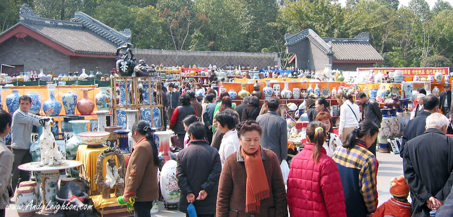 Crowds of people browsing around the displays of vases and pottery. Renmin Park, Chengdu, China