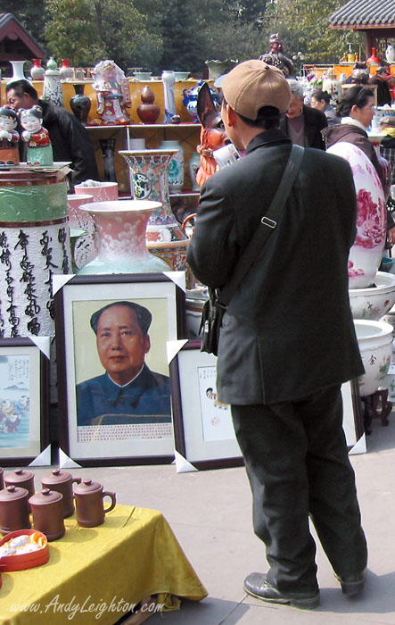 A man looks on at a framed picture of Mao Zedong