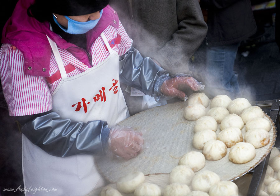 A women shop assistant dressed in the shops pink colour prepares the freshly steamed king dumplings or mandu ready for sale. Namdaemun Market, Seoul, South Korea