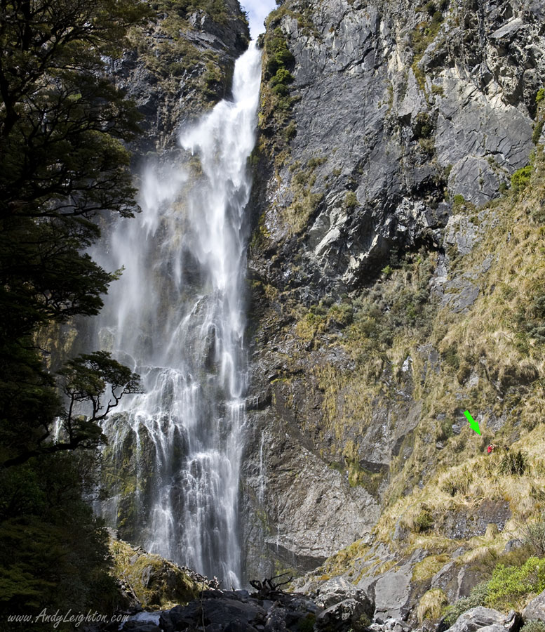 A man in a red jacket is dwarfed by the 130 metres high Devils Punchbowl Waterfall in Arthurs Pass National Park, New Zealand