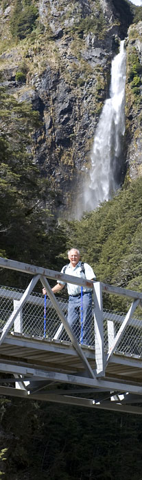 A man walks along the lower walkbridge with the Devils Punchbowl Waterfall up high in the mountainous background. Arthurs Pass National Park, New Zealand