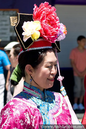 A red costumed Chinese woman with a red and yellow flowered headdress is part of the parade walking along James Street. Australian Mulan Arts & Culture Association (AMACA), WA Chinese Woman's Federation (WACWF) Chinese New Year 2013, Northbridge, Perth, Australia