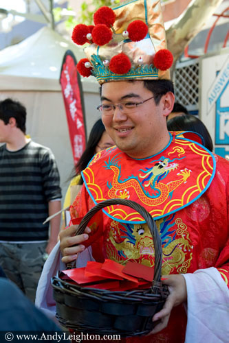 A colourfully red costumed Chinese man gives out small red brochures from a woven basket. Chinese New Year 2013, Northbridge, Perth, Australia
