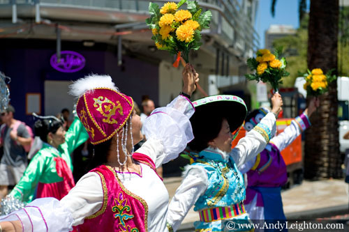 Three colourfully costumed chinese women hold yellow flowers high in the air as they march in line along James Street. Australian Mulan Arts & Culture Association (AMACA), WA Chinese Woman's Federation (WACWF) Chinese New Year 2013, Northbridge, Perth, Australia
