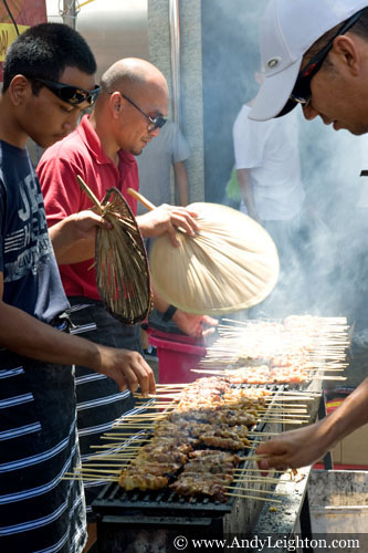 Cooks use bamboo fans to tend to a smoky row of meat kababs. Chinese New Year 2013, Northbridge, Perth, Australia