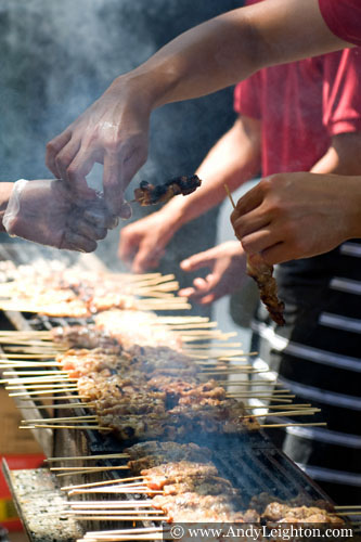 Two cooks pass kababs to each other, behind are more kebabs grilling over a hot smoky barbecue. Chinese New Year 2013, Northbridge, Perth, Australia