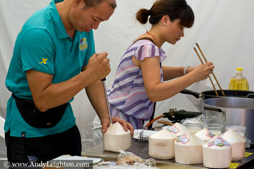 A man pushes a hole into a manufacted round shaped coconut. After a straw will be inserted for customers to drink the coconut milk. Chinese New Year 2013, Northbridge, Perth, Australia