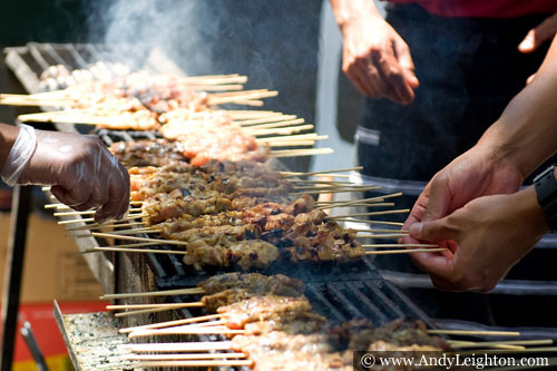 Two cooks turn the kababs grilling over a hot smoky barbecue to prevent burning. Chinese New Year 2013, Northbridge, Perth, Australia
