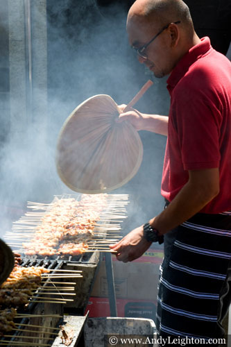 A cook fans away the barbecue smoke while he turns his grilling kababs. Chinese New Year 2013, Northbridge, Perth, Australia