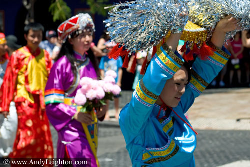 A blue costumed boy holds flowing silver paper strands high in the air as he walks along James Street. Australian Mulan Arts & Culture Association (AMACA), WA Chinese Woman's Federation (WACWF) Chinese New Year 2013, Northbridge, Perth, Australia