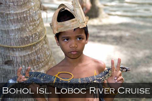 A young Philippines boy wearing grass headwear holds a lizard. Loboc River, Bohol Island, Philippines