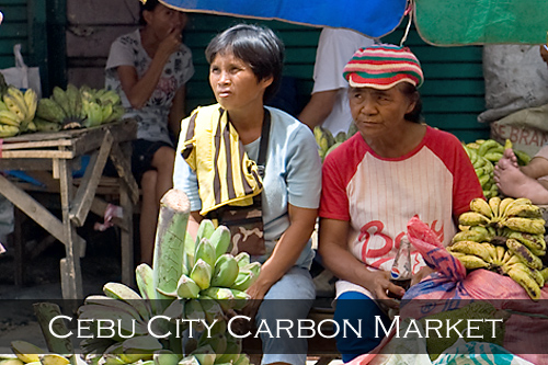 A group of sellers sit under a colourful umbrella surrounded by potatoes, bananas and other prickly fruit. Carbon Market, Cebu City, Philippines