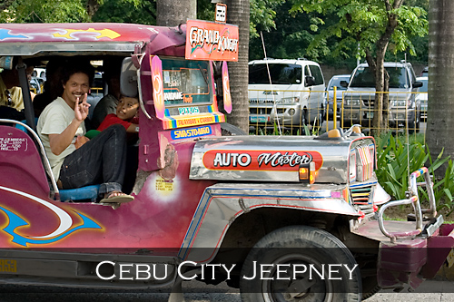 A man smiles and hand signs towards the camera from the passenger seat of a purple coloured jeepney. Cebu City, Philippines