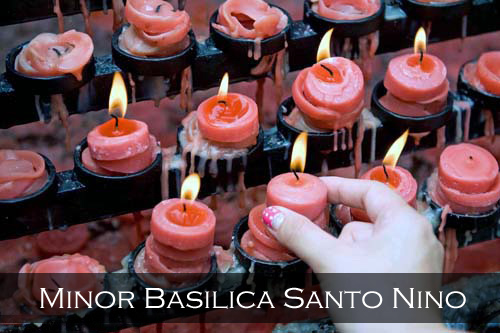 A girls hand places a newly lit red prayer candle back into its holder. Basilica Minore del Santo Nino Church, Cebu City, Philippines
