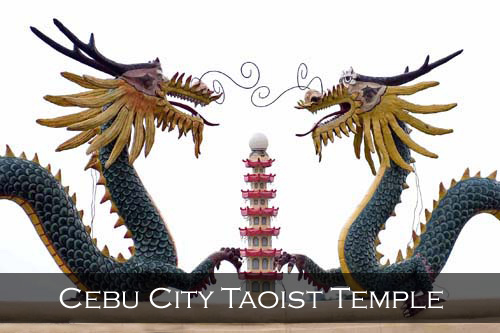 On the roof two green and yellow dragon statues face each other with a small seven story pagoda between them. Taoist Temple, Cebu City, Philippines