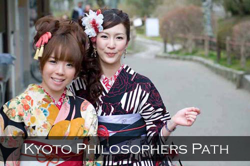 Two girls in colourful kimonos smile for the camera. Philosopher's Walk Path, Kyoto, Japan