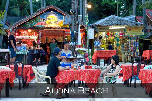 A couple enjoy the outdoor beach table service of a restaurant along Alona Beach. Panglao Island, Philippines