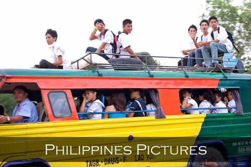 A country school bus filled inside with students, and others riding on top of the bus. Panglao Island, Philippines