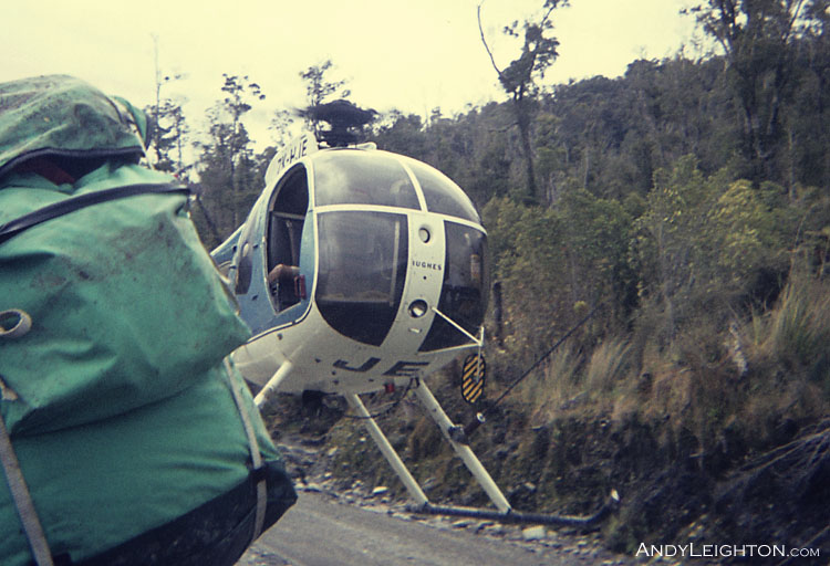 The Hughes 500 helicopter picks up searchers on a gravel road for ferrying to another search area. Arahura River Valley, Westland, New Zealand. ZK-HJE, Bill Hendy (pilot)