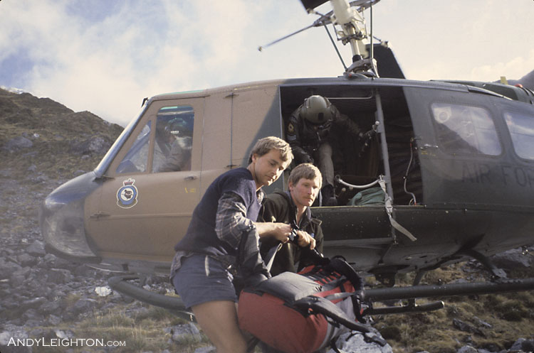 The last of our packs are passed out of the hovering Iroquois helicopter by the Air Force crewman. Waitaha River Valley, Westland, New Zealand. Bob Bird, Stephen Langridge.