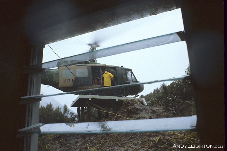 A view through the hut window of the searchers in the Iroquois helicopter on the County Stream Hut's helipad. County Stream Hut, Waitaha River Valley, Westland, New Zealand