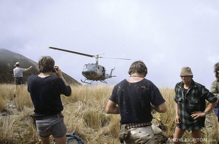 An Air Force Iroquois helicopter approaches to land in the tussock grass on the open mountain tops. Paparoa Ranges, Westland, New Zealand. Hacky Sims, Pat Coll