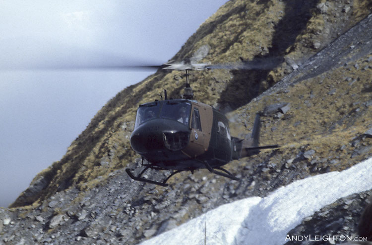 An Air Force Iroquois helicopter approaching to land and pick up searchers in a mountainous area of Westland. New Zealand