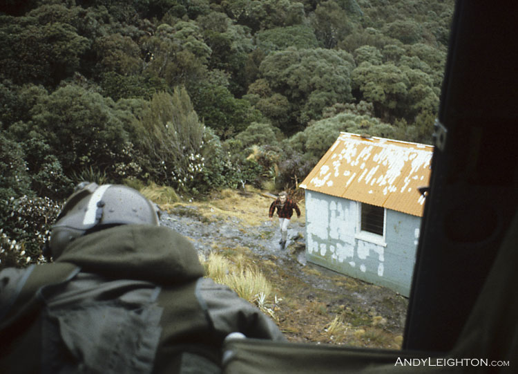 A view from inside the Iroquois helicopter past the crewman of the County Stream Hut. A quick early helicopter visit to the hut, to check the hut logbook for any sign of the missing hiker. County Stream Hut, Waitaha River Valley, Westland, New Zealand. Bob Bird