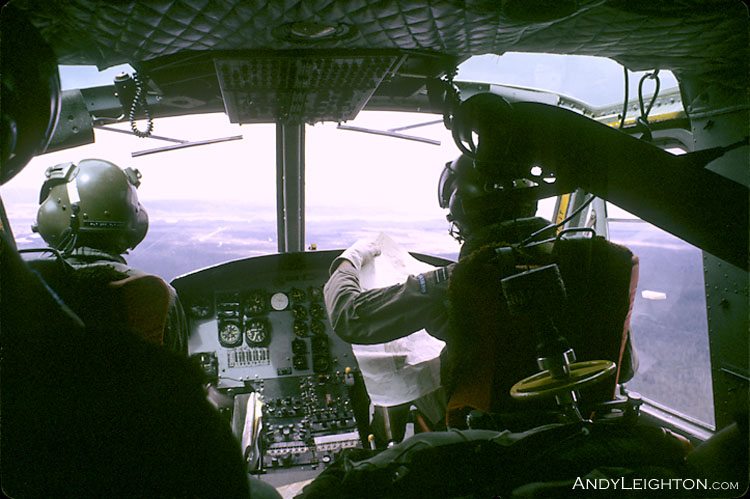 A view from inside the cockpit of the two Iroquois helicopter pilots, one reading a map. Ahaura, Westland, New Zealand
