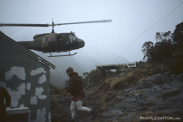 The Iroquois helicopter on final approach to the County Stream Hut's wooden helipad. County Stream Hut, Waitaha River Valley, Westland, New Zealand. Bob Bird