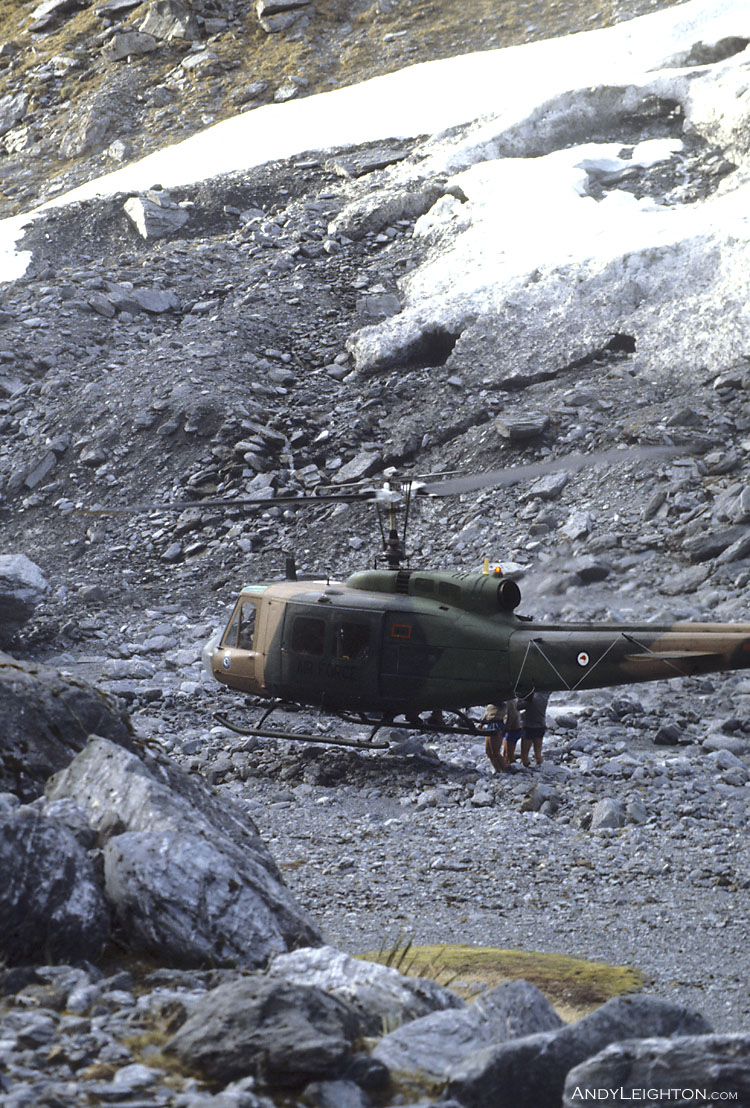 An Iroquois helicopter hovers above rocky ground as searchers climb on board. Waitaha River Valley, Westland, New Zealand