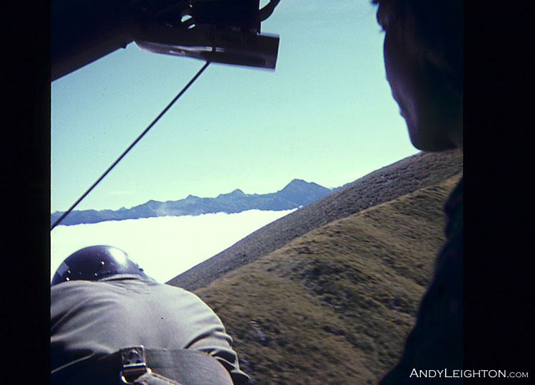An Iroquois helicopter crewman looking for a safe landing spot for the pilots, so searchers can be dropped off onto the open mountain tops. Kopara Valley, Westland, New Zealand. Tony Ellery