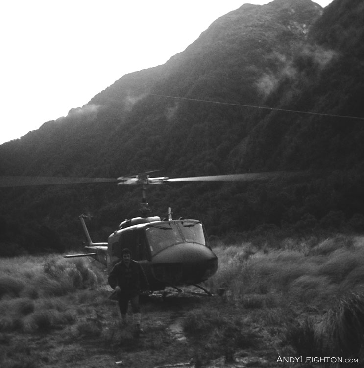 After a heavy downpour of rain, an Air Force Iroquois Helicopter lands and drops of Search Co-ordinator Terry Sweetman in the clearing near to the Cedar Flats hut. Toaroha River Valley, Westland, New Zealand.
