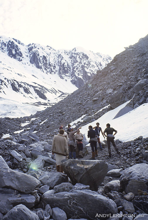 With a backdrop of icy mountains, searchers discuss the next area to be searched for any signs of the missing hiker. Waitaha River Valley, Westland, New Zealand. Stephen Langridge.