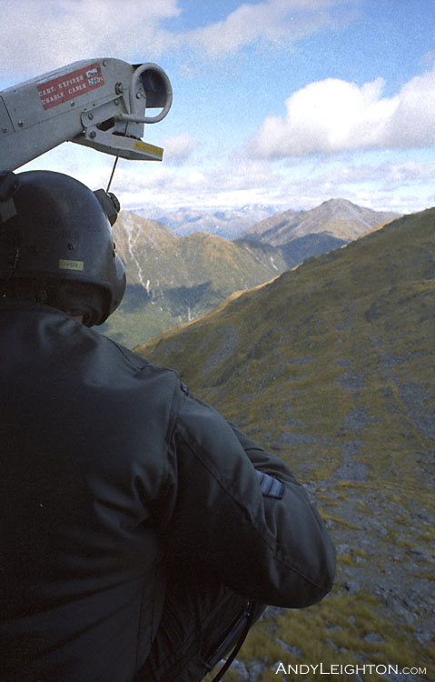 A view over the Iroquois helicopter crewman's shoulder as we pass close over a mountain ridge. Kopara, Westland, New Zealand