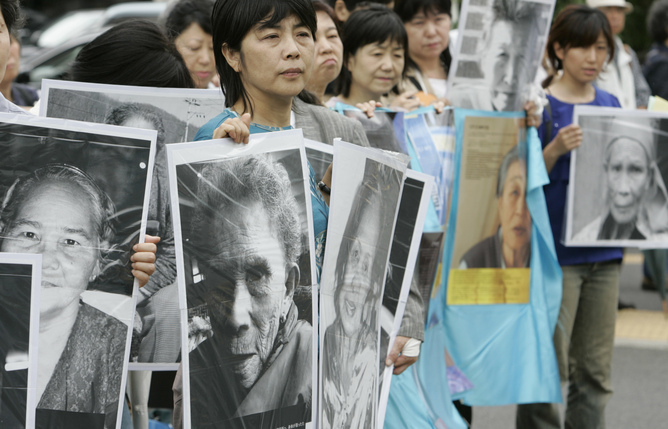 Japanese protesters hold portraits of former comfort women at a rally, demanding the Japanese government compensate and apologise to women forced to work in wartime brothels during World War II, near the Diet building in Tokyo June 14, 2007. REUTERS/Kim Kyung-Hoon (JAPAN) - RTR1QS4M