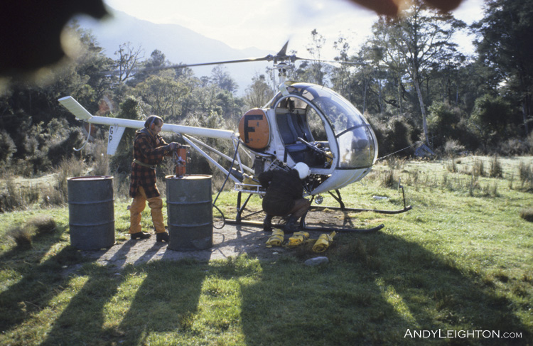 Helicopter crew refueling the Hughes 300 after a morning's deer hunting. Waikiti Downs, Westland, New Zealand. ZK-HGP, Tom Trevors (pilot), Andy Nolan (shooter)