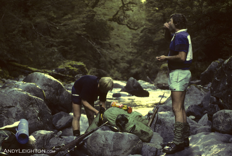A welcome break after a hard days walk along the upper Trent River with pack and rifle. Darkness will be within the hour, but we still have an hour and a half walking left to reach the Lagoon hut, the last half hour was done by torchlight. Westland, New Zealand. Garry Turnbull, Pete Gurden