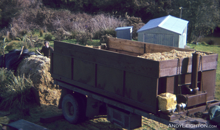 In the early sphagnum moss days before drying onsite became common. Here a truck load of wet sphagnum moss is forked onto a TNT transport trailer for cartage to a drying facility. Marsden, Westland, New Zealand. John Leighton