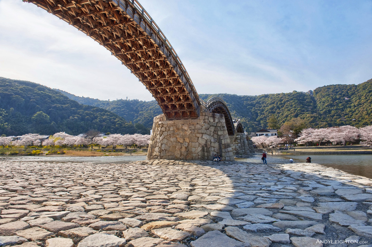 HDR view from below the Kintai Kyo Bridge, exposing the wooden support framework, and the arched bridge casting a shadow onto the flat rocks below. Iwakuni, Japan