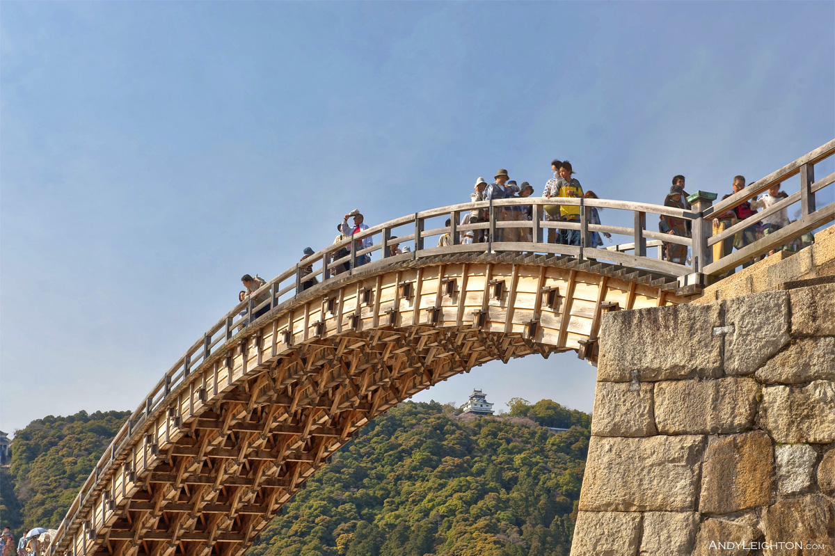HDR of people walking over the Kintai Kyo Bridge, beneath them the structural wooden framework can be clearly seen, Iwakuni, Japan